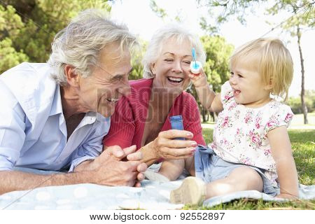 Grandparents And Granddaughter Playing In Park Together