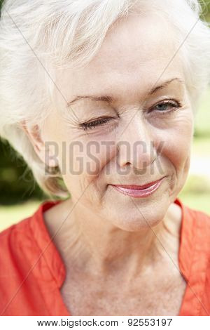 Head And Shoulders Portrait Of Winking Senior Woman