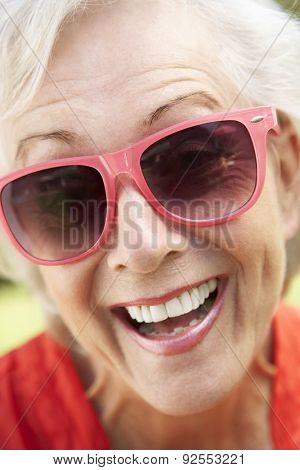 Head And Shoulders Portrait Of Smiling Senior Woman Wearing Sunglasses