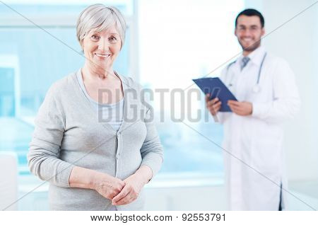 Smiling mature woman looking at camera with doctor on background