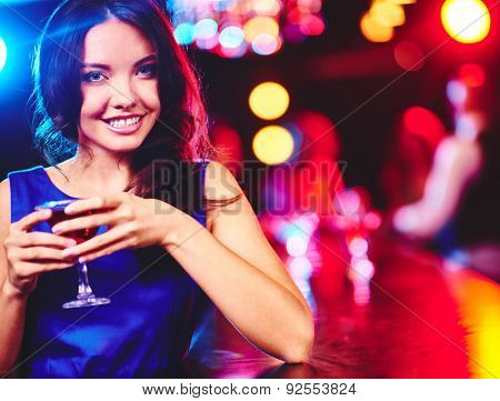 Happy young woman with glass of martini looking at camera