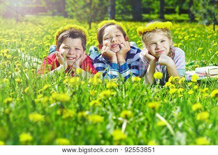 Happy children with dandelion wreaths having rest in natural environment