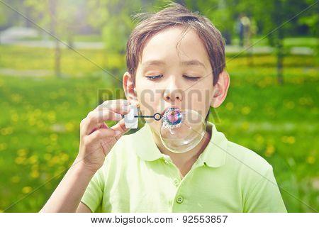 Handsome boy blowing soap bubbles in park
