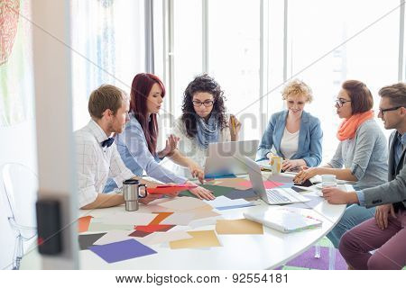 Creative businesspeople analyzing photographs at conference table in office