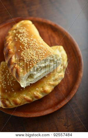 Pieces of fatayer, an arabic puffed bread placed on wooden plate.