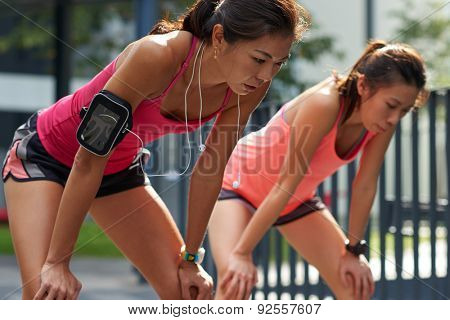 exhausted sporty asian chinese women runners after fitness running workout outdoors