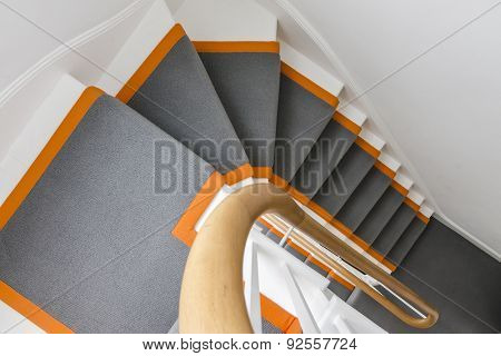 beautiful white staircase with grey carpet and orange highlights