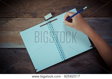 Hand writing in open notebook on table - hand focus