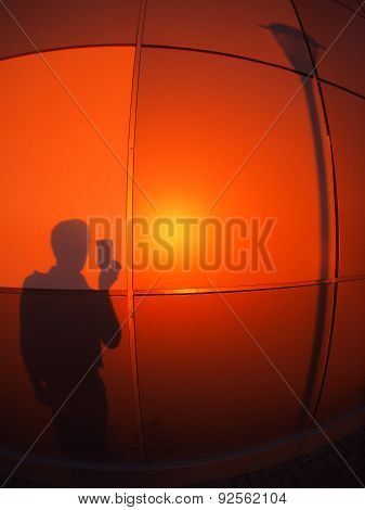 The Silhouette Of A Man On A Red-orange Wall,