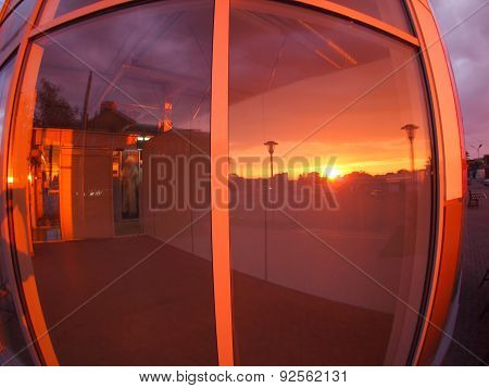 Cityscape At Sunset, Which Is Reflected In The Window