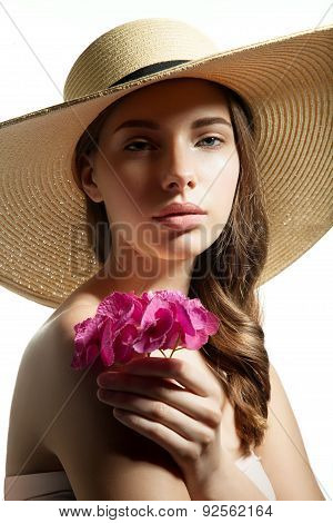 Girl with a flower in her hand and a straw hat