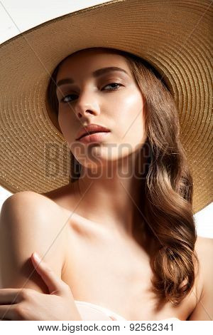 Close-up portrait of a young woman in straw hat