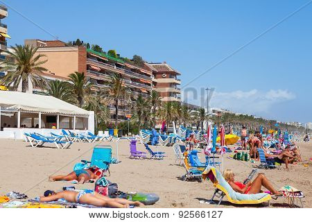 Tourists Relaxing On Sandy Beach In Spain