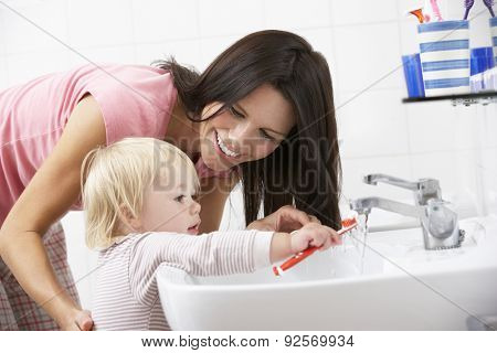 Mother And Daughter In Bathroom Brushing Teeth