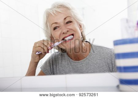 Senior Woman In Bathroom Brushing Teeth