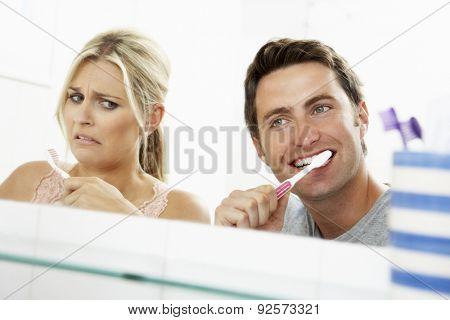 Couple In Bathroom Brushing Teeth