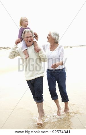 Grandparents And Granddaughter Walking Along Beach Together