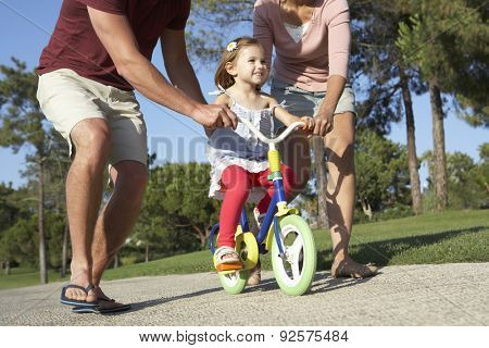 Parents Teaching Daughter To Ride Bike In Park