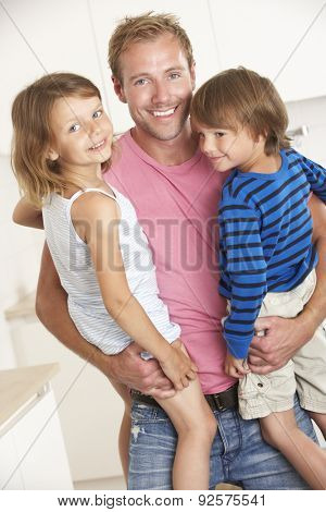 Father Giving Children Cuddle At Home