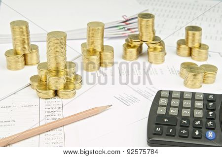 Pencil And Calculator With Pile Of Gold Coins