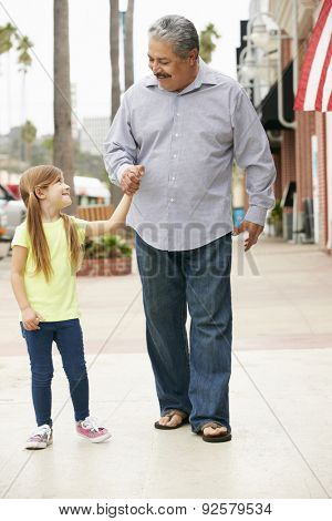 Grandfather With Granddaughter Walking Along Street