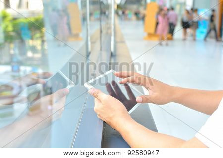 Male Hand Using Mobile Phone In Modern Building Background