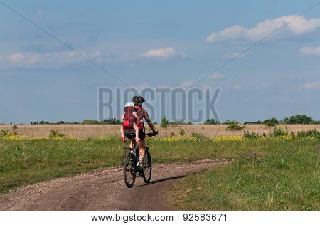 Young Mother With Her Baby Mountain Bike Ride On Dirt Road.