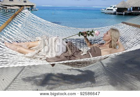 the woman in long dress with a rose in hand lies in a hammock on background of the sea
