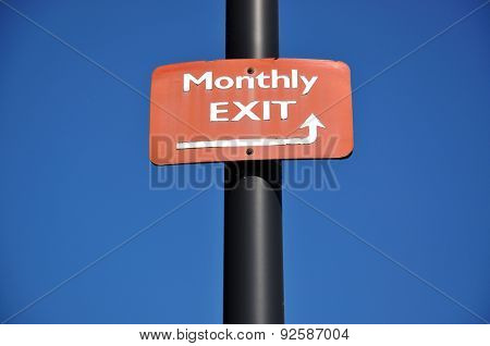 Monthly exit road sign against blue sky