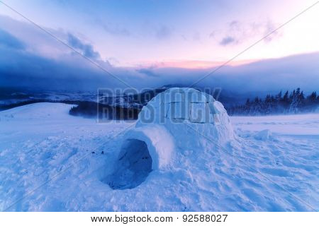 Colorful winter sunset in the Carpathian mountains. Snowy ihloo on a foreground. Ukraine, Europe.