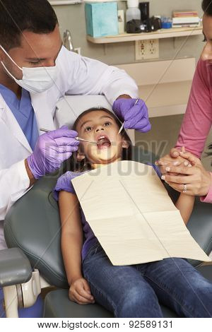 Young Girl Having Check Up At Dentists Surgery With Mother