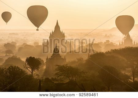 Air balloons flying over pagodas at misty dawn in the plain of Bagan, Myanmar (Burma)