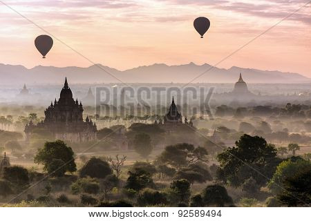 Air balloons flying over pagodas at misty morning in the plain of Bagan, Myanmar (Burma)