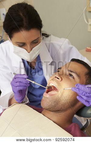 Man Having Check Up At Dentists Surgery