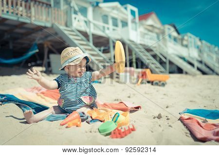 baby girl sitting in the sand on the beach playing and laughing