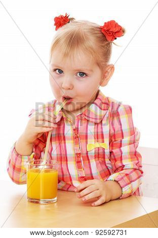 Funny little girl is drinking orange juice through a straw while