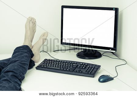 legs and feet on a desk with computer with a white screen