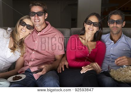 Friends Sitting On Sofa Watching TV Wearing 3-D Glasses