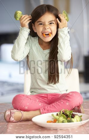 Girl Making Devil Face With Plate Of Fresh Vegetables
