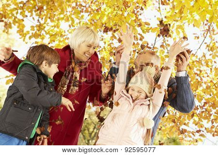 Grandparents And Grandchildren With Leaves In Autumn Garden