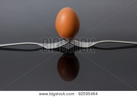Egg Balancing On Two Interlocking Forks With Reflection On Shiny Surface