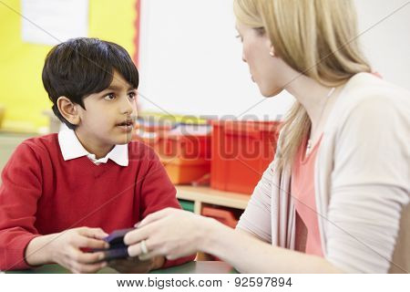 Teacher Helping Male Pupil With Maths At Desk