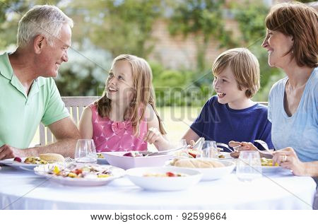 Grandparents With Grandchildren Enjoying Outdoor Meal