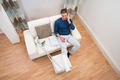 pic of crutch  - High Angle View Of A Man With Crutches Sitting On Sofa Talking On Cellphone - JPG