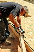 pic of worm  - Building contractor worker using hand held worm drive circular saw to cut boards on a new home construciton project - JPG