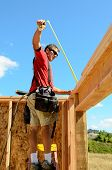 image of rafters  - Building contractor worker measuring out the top plate of the wall in preparation for the rafter on the second floor on a new home construciton project - JPG