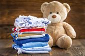 picture of baby bear  - Baby clothes stack and teddy bear on a wooden table - JPG