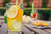stock photo of infusion  - Infused fruit water cocktails and green vegetable smoothies over a wooden table outdoors - JPG