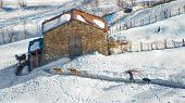 picture of dairy barn  - Farmer of the Italian Alps to the barn with farm animals with wood in shoulder - JPG