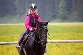 stock photo of horse girl  - young girl is training with black horse - JPG